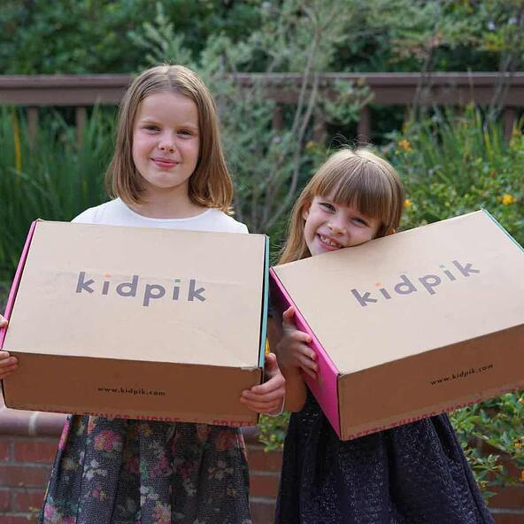 Image of two young girls holding big Kidpik boxes