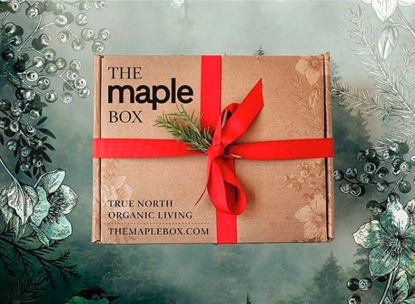 Image of a Maple Box subscription package with red ribbon and pine
