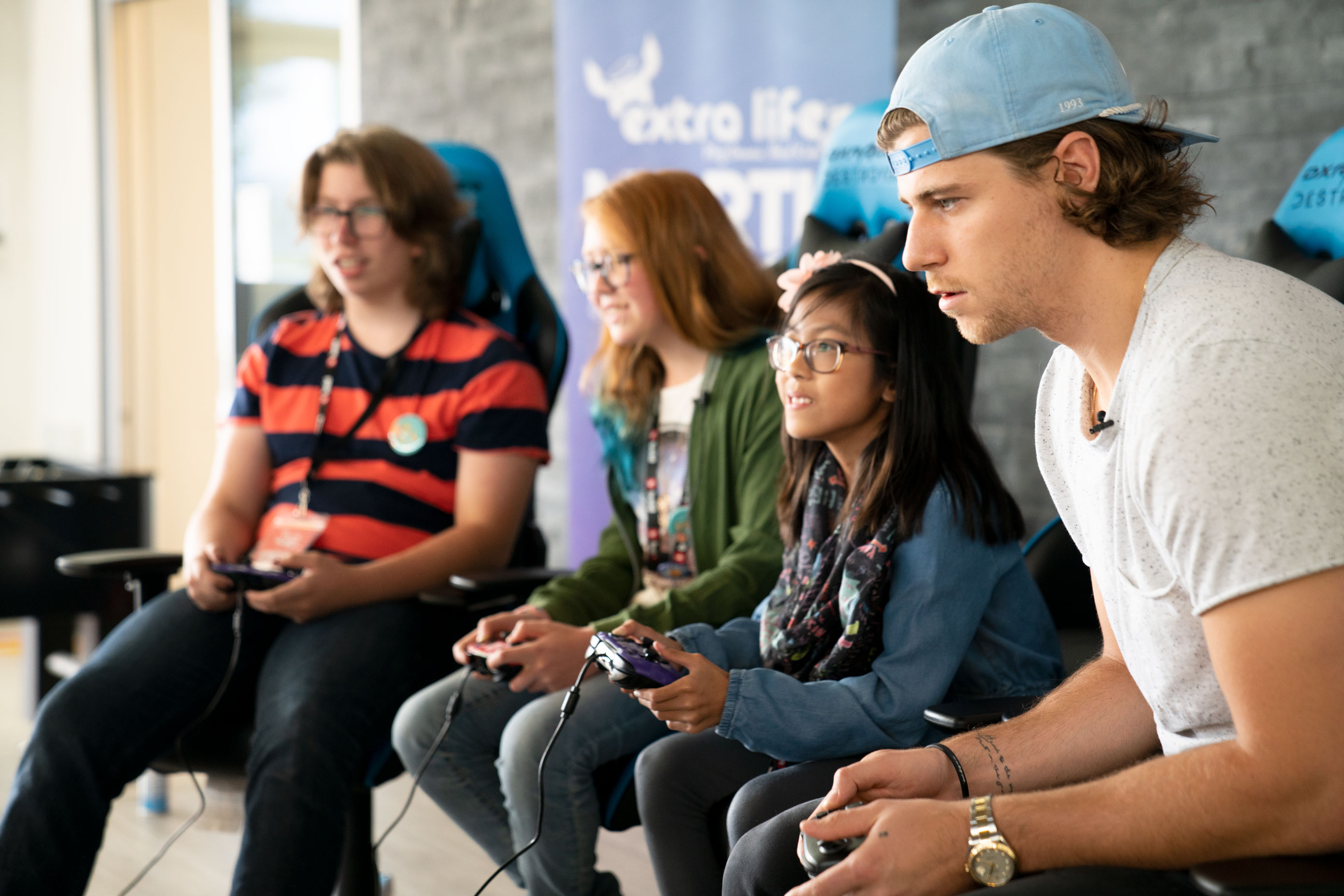 Children playing video games with Winnipeg Jets' player, Nate Beaulieu